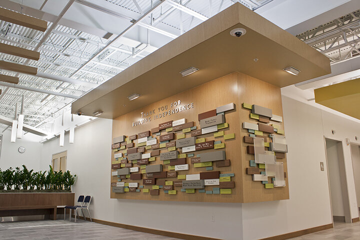 A wooden display wall with placards displaying major donor names