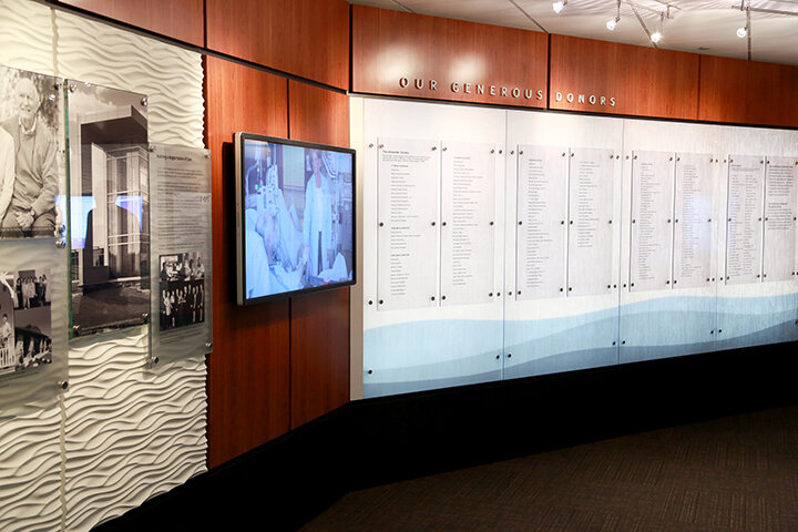 donor thank you wall with glass panels with lists of donor names and a television screen with a video still of a hospital patient